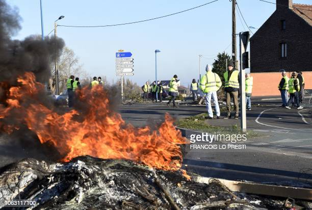 Demonstrators of the Yellow Vests movement stand by a fire on November 18 2018 on a roundabout in DouchylesMines near Valenciennes northern France a...