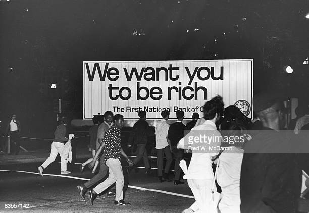 Demonstrators on Michigan Avenue pass a billboard that reads 'We Want You To Be Rich' during protests at the Democratic National Convention Chicago...