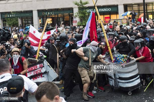 Demonstrators opposed to a farright rally block a street as police try to dislodge them near the White House August 12 2018 in Washington DC one year...