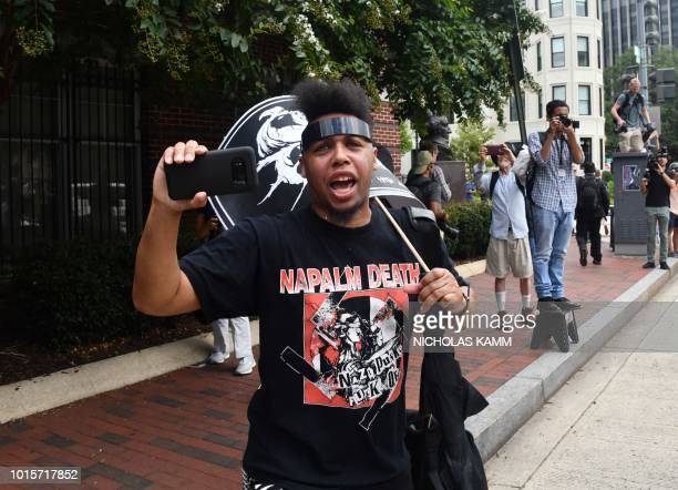 Demonstrators opposed to a farright rally hold signs at Lafayette Park opposite the White House August 12 2018 in Washington DC one year after the...