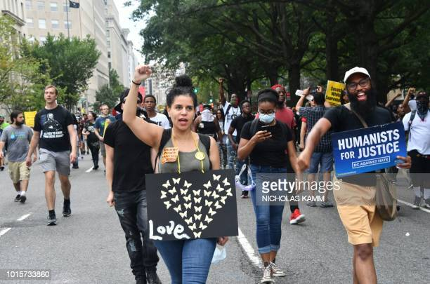 Demonstrators opposed to a farright rally march and hold signs at Lafayette Park opposite the White House August 12 2018 in Washington DC one year...