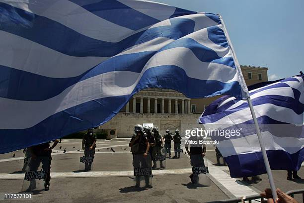 Demonstrators outside Greek Parliament hold the flag of Greece as they gather during a protest against plans for new austerity measures on June 28...