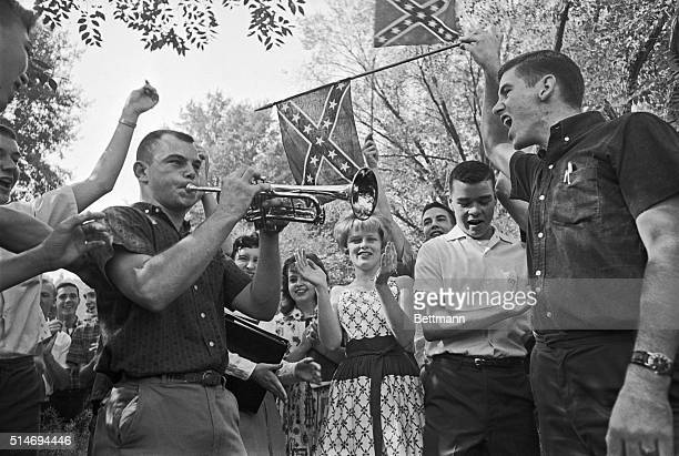 Demonstrators outside of West End High School in Birmingham, Alabama sing Dixie as a student plays the tune on a trumpet during an anti-desegregation...