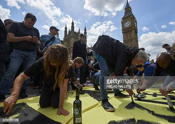 Demonstrators paint a banner as they take part in a protest against the Conservative government's austerity measures in central London on May 30 2015...