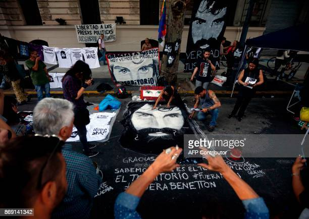 Demonstrators paint a portrait of late activist Santiago Maldonado in the street during a march to demand justice three months after his...