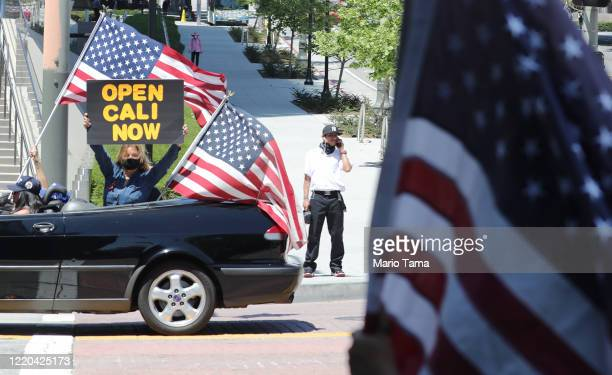 Demonstrators participate in a car caravan protest outside City Hall as a pedestrian looks on calling on California officials to reopen the economy...
