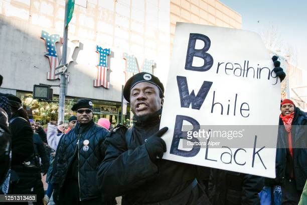 Demonstrators participate in a march against police brutality in the Jamaica neighborhood of Queens New York New York December 9 2006 One man holds a...