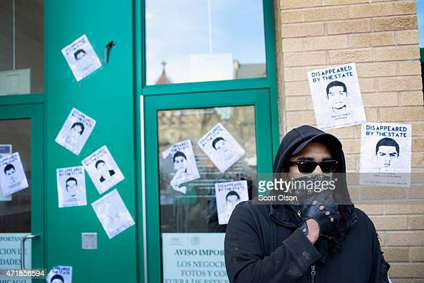 Demonstrators participating in a May Day march paste missing person posters on the front of the Mexican Consulate on May 1 2015 in Chicago Illinois...