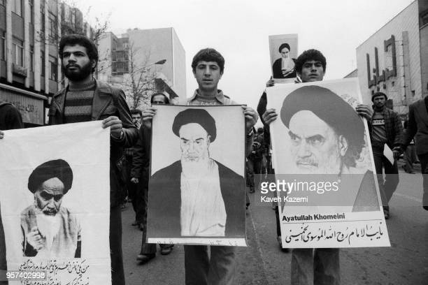Demonstrators participating in the protests on Ashura Day carry banners with pictures of Ayatollah Khomeini in Tehran during the Iranian Revolution...