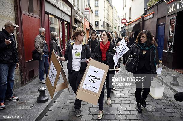 Demonstrators paste flyers on walls as they take part in a protest against sexual and verbal harassment on April 25 in Paris A group of protesters...