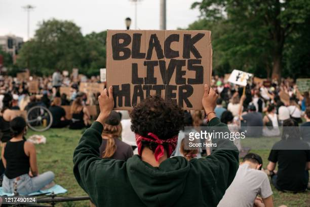 Demonstrators pause for a moment of silence during a protest over the killing of George Floyd by a Minneapolis Police officer in McCarren Park in the...
