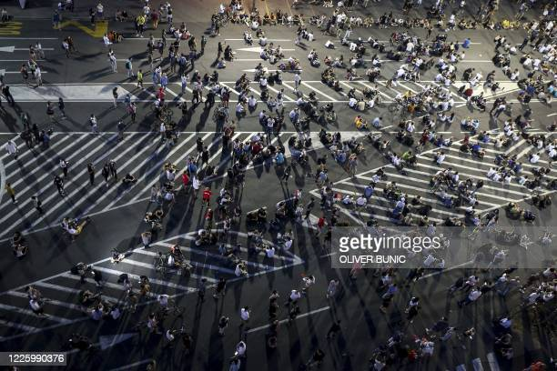 Demonstrators peacefully sit on the street in front of the parliament during a protest in Belgrade on July 9, 2020. - Thousands of people protested...