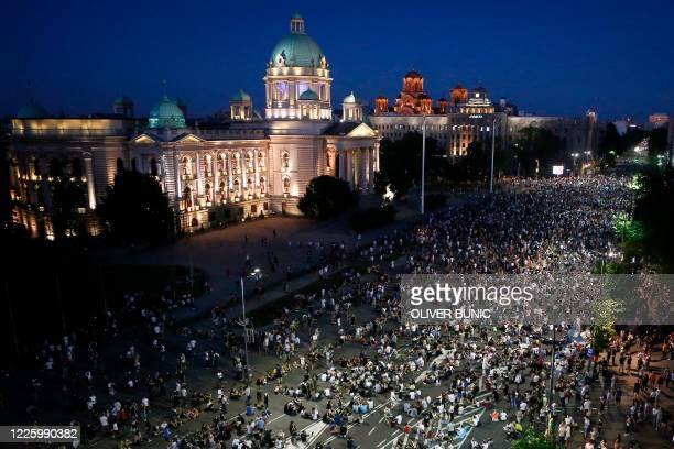 Demonstrators peacefully sit on the street in front of the parliament during a protest in Belgrade on July 9 2020 Thousands of people protested on...