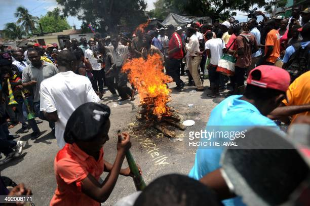 Demonstrators perform a voodoo ceremony before a protest against the government of President Michel Martelly during Haitian Flag Day in PortauPrince...
