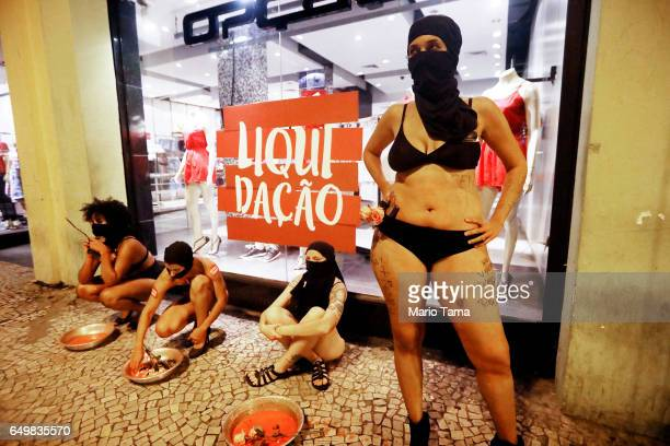 Demonstrators perform in front of a clothing shop with a sign in Portuguese reading 'liquidation' at a protest on International Women's Day on March...