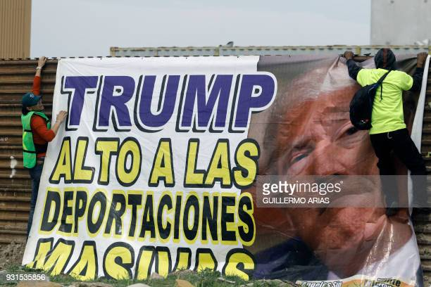 Demonstrators place a banner reading 'Trump stop massive deportations' during a protest against US President Donald Trump's migration policies on the...