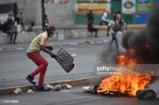 Demonstrators place a tire barricade during clashes with Haitian police in PortauPrince February 15 on the ninth day of protests against Haitian...