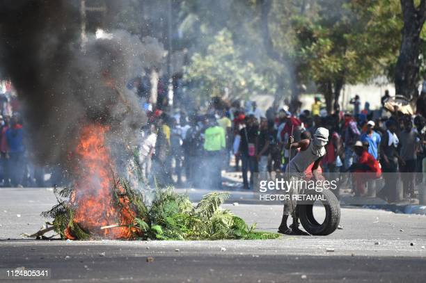 Demonstrators place barricades during clashes, in front of the National Palace, in the centre of Haitian Capital Port-au-Prince, on February 13,...