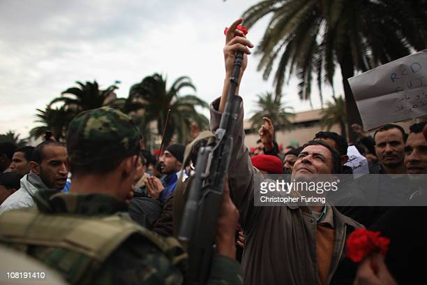 Demonstrators place flowers in the barrels of soldiers guns as Tunisians take to the streets again to protest for changes in Tunisia's new government...