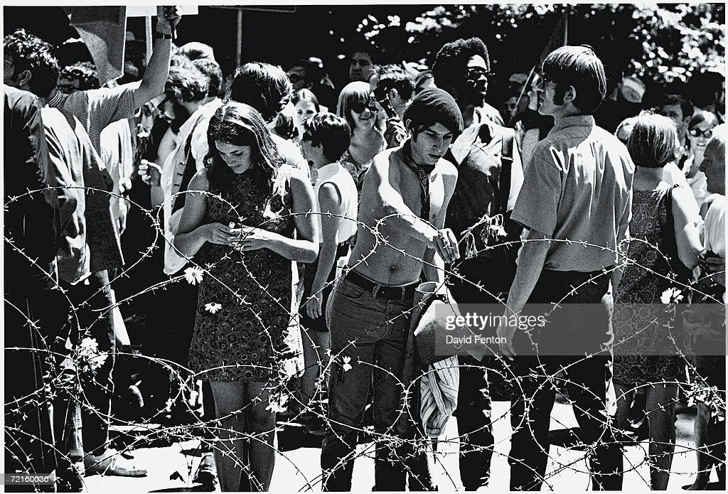 Demonstrators place flowers on a barbed wire fence in People's Park on the campus of the University of Berkeley, California, May 30, 1969. The demonstrators, part of the 30,000 out of Berkeley's 100,000 residents, gathered and marched to protest the May 15th killing by police of an unarmed spectator at an earlier demonstration and the subsequent occupation of their city by the National Guard.