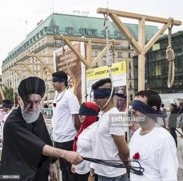 Demonstrators pose in a mock execution in front of Brandenburg Gate in Berlin Germany 26 August 2017 The National Resistance Council in Germany has...