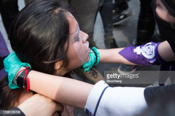 Demonstrators pour milk on a woman's face after police fired tear gas during a rally on International Women's Day in Mexico City Mexico on Friday...