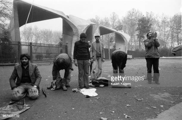 Demonstrators pray in front of the university while participating the protests on Ashura Day in Tehran during the Iranian Revolution 11th December...