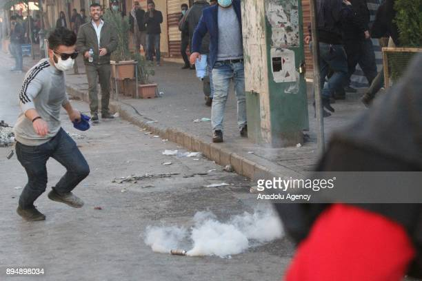 A demonstrators prepares to kick a tear gas can back at riot police as they clash within antigovernment protests in Sulaymaniyah Iraq on December 18...