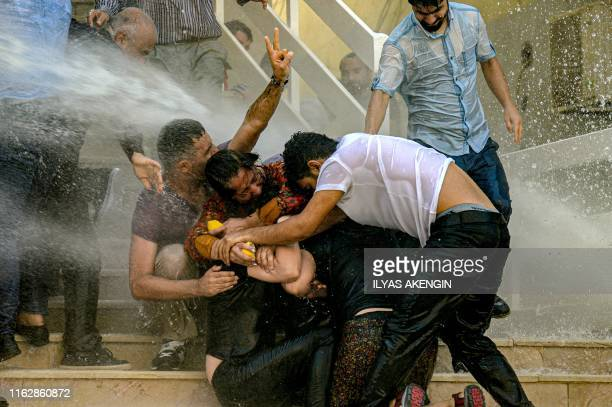 Demonstrators protect each other as they are hit by water cannon during a protest against the replacement of Kurdish mayors with state officials in...