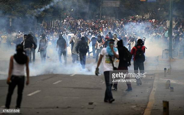 Demonstrators protect their faces from tear gas during an antigovernment protest in east Caracas on March 12 2014 A young man was shot dead early...