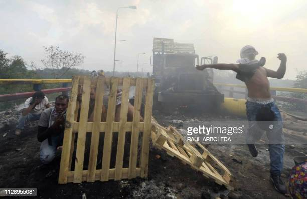 TOPSHOT Demonstrators protect themselves after a truck was set on fire at the Francisco de Paula Santander international bridge Bridge linking Cucuta...