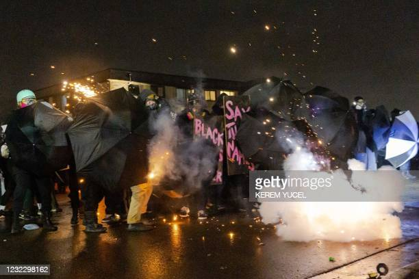 Demonstrators protect themselves with umbrellas against tear gas and pepper balls outside the Brooklyn Center police station as they protest the...