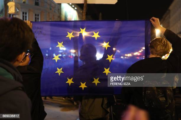 Demonstrators protest against Hungarian Prime Minister Viktor Orban's government with an EU flag on Oktogon square on April 15 2017 in downtown...