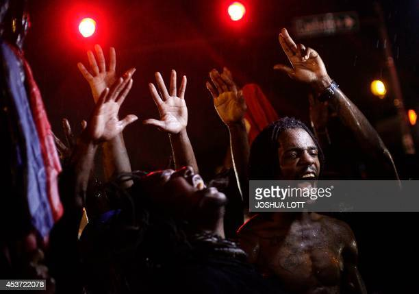 Demonstrators protest against the August 9 police shooting of 18yearold Michael Brown by holding their hands up while gathered on the streets of...