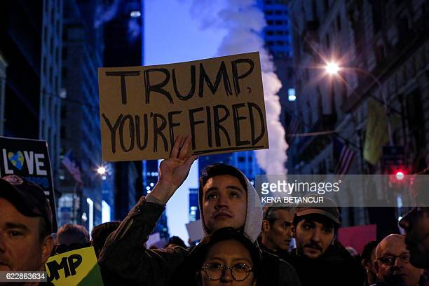 TOPSHOT Demonstrators protest against US Presidentelect Donald Trump in front of Trump Tower on November 12 2016 in New York Americans spilled into...