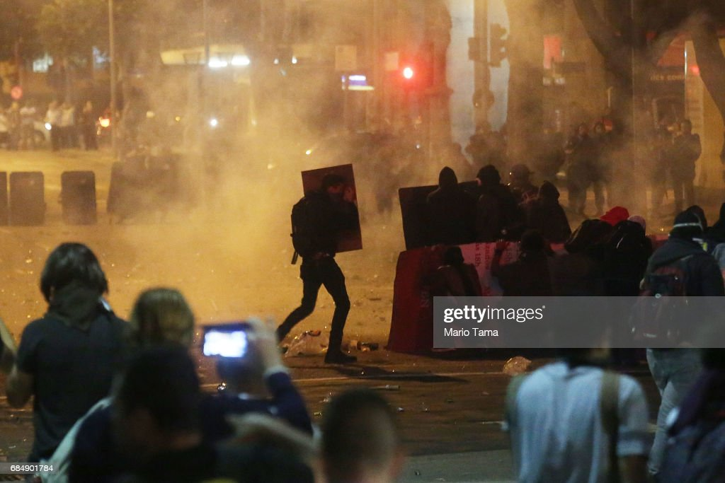Demonstrators protest amidst tear gas during an anti-Temer protest on May 18, 2017 in Rio de Janeiro, Brazil. Thousands of protestors hit the streets of Rio in the aftermath of a recording allegedly revealing President Michel Temer endorsing bribery payments.