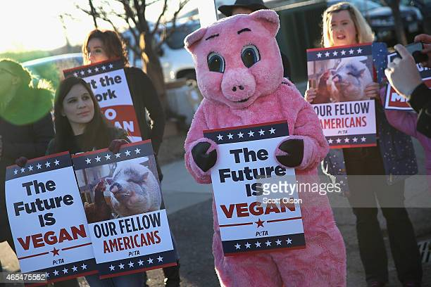 Demonstrators protest as people arrive for the Iowa Ag Summit on March 7 2015 in Des Moines Iowa The summit allows the invited speakers many of whom...