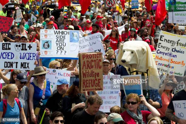 Demonstrators protest as they march on Pennsylvania Avenue during the People's Climate March in Washington DC on April 2017 / AFP PHOTO / Jose Luis...