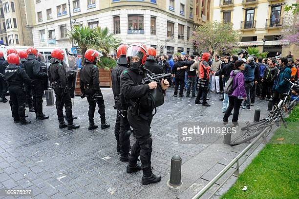 Demonstrators protest in front of members of the Ertzaintza Basque Police after six members of the Basque proindependence youth organization SEGI...