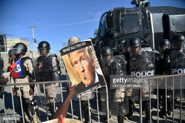 Demonstrators protest in front of the Haitian national police near the US Embassy in PortauPrince on January 22 during a protest against the...
