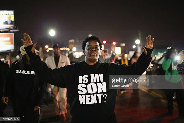 Demonstrators protest in front of the police station on March 12 2015 in Ferguson Missouri Two police officers were shot yesterday while standing...