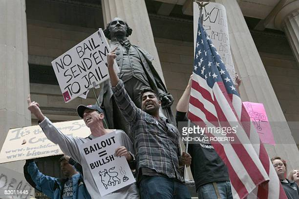 Demonstrators protest next to a statue of George Washington at the Federal Hall National Memorial on Wall Street against the USD 700 billion Wall...