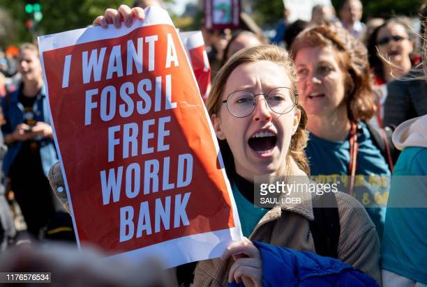 Demonstrators protest the IMF and World Bank's investments in fossil fuels and urge them to confront climate change as they march outside the World...