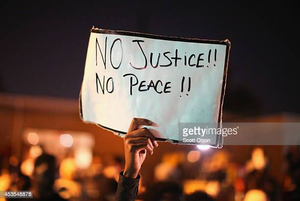 Demonstrators protest the killing of teenager Michael Brown on August 12 2014 in Ferguson Missouri Brown was shot and killed by a police officer on...