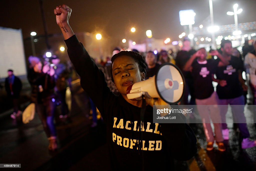 Demonstrators protest the shooting death of Michael Brown November 23, 2014 in St. Louis, Missouri. Brown, a 18-year-old black male teenager was fatally wounded by Darren Wilson, a white Ferguson Police officer on August 9, 2014. A 12-member grand jury is reviewing evidence to decide whether or not to indict Wilson on charges.