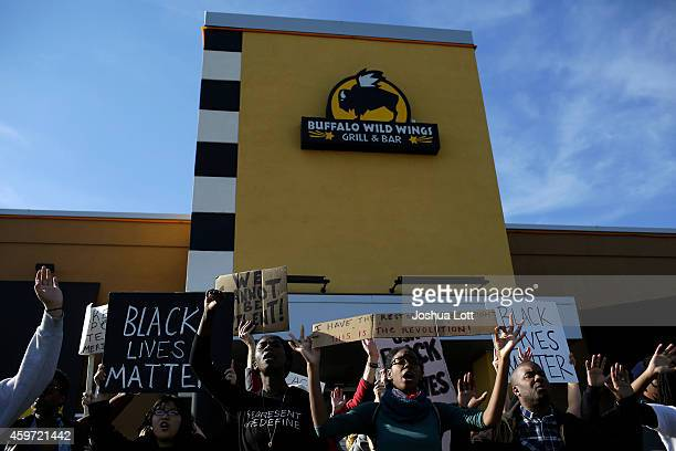 Demonstrators protest the shooting death of Michael Brown stand outside Buffalo Wild Wings November 29 2014 in Brentwood Missouri Brown a 18yearold...