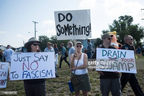 Demonstrators protest the visit of US President Donald Trump to the site of the mass shooting in Dayton, Ohio, on August 7, 2019. - Nine people were...