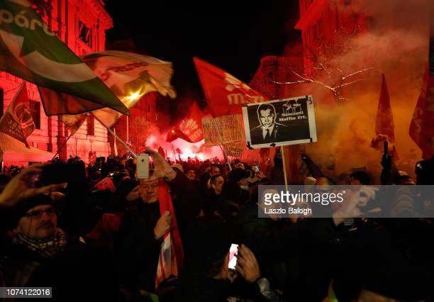 Demonstrators protesting against recent legislative measures introduced by the government of Hungarian Prime Minister Viktor Orban stand outside...