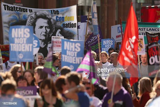 Demonstrators protesting against the Government's cuts to the NHS march past the Manchester Central centre which is hosting the Conservative Party...