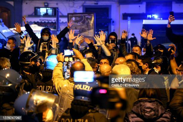 Demonstrators protesting against the measures taken to control the novel coronavirus covid-19 pandemic face Italian anti-riot policemen in front of...